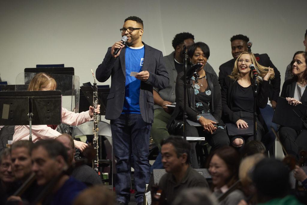 Joseph Garnier welcomes people to community sing.